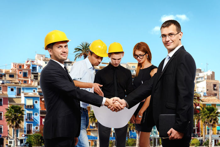 Business people shaking hands, finishing up a meeting. Construction theme ARCHITECT Business Meeting Construction Man Meeting Plan Suit Work Worker Blueprints Builder Caucasian Confident  Construction Industry Construction Work Construction Worker Engineer Engineering Foreman Group Of People Hardhat  Paper People Project Young Adult