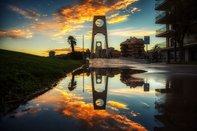 Reflection of building in puddle during sunset