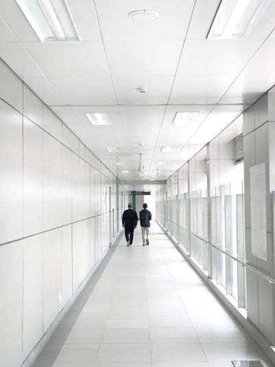 Rear view of men walking in corridor