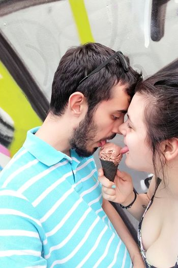 Couple licking ice cream outdoors