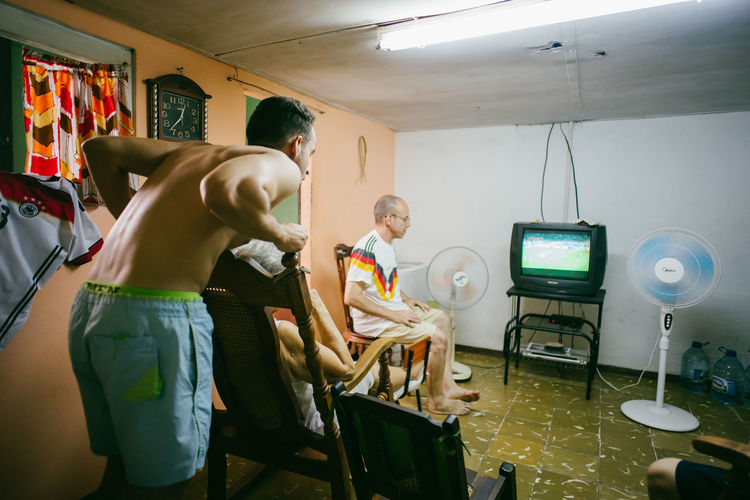 We watched the Worldcup in Cuba~ Adult Care Females Illuminated Indoors  Lifestyles Lighting Equipment Love The Game Males  Men Occupation People Preparation  Real People Standing Technology Togetherness Women Working