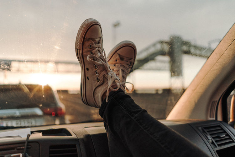 Low section of person wearing canvas shoes on car window