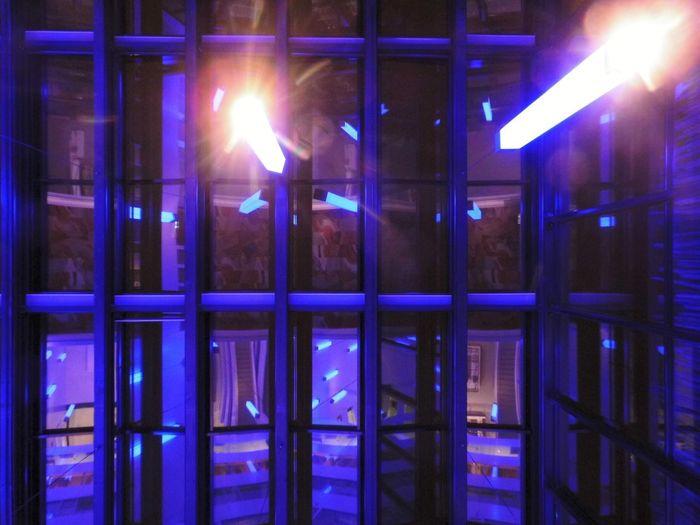 Illuminated lights on glass window at night