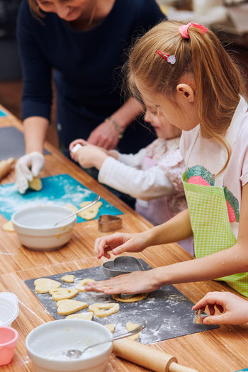 Midsection of woman assisting girls in making cookies on table