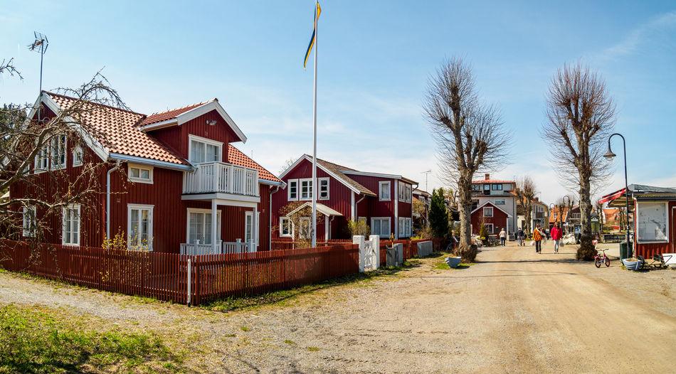 Houses by street amidst buildings against sky