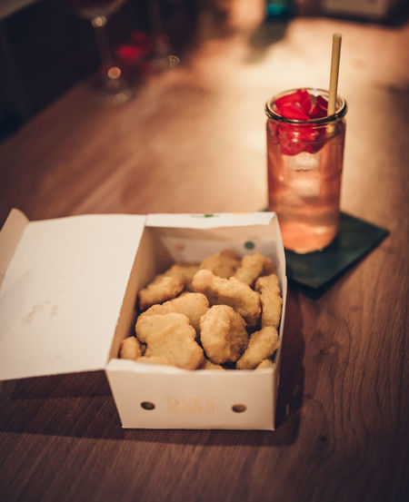 Box of chicken nuggets and a alcoholic drink on wooden table Chicken Cocktail Nuggets Strange Food Barkeeper Chicken Mcnuggets Drink Fastfood Food Food And Drink Indoors  Longdrink No People Ready-to-eat Refreshment Table