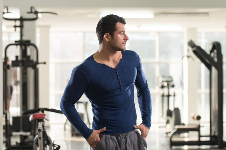 Muscular man looking away while standing in gym