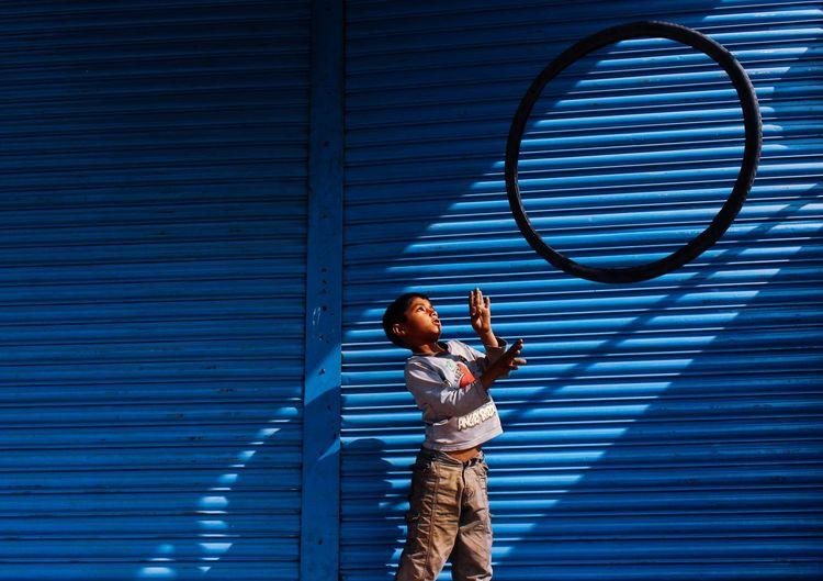 Full length of man standing against blue wall