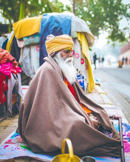 Side view of sadhu sitting on sidewalk in city