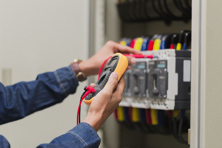 Midsection of man checking electrical equipment
