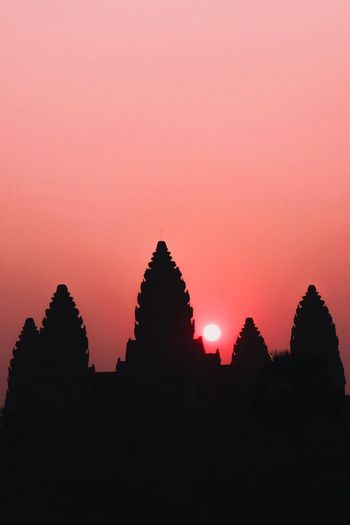 Silhouette of temple against building during sunset