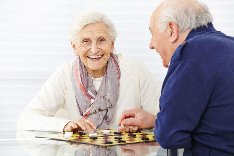 Smiling senior couple playing board game at home