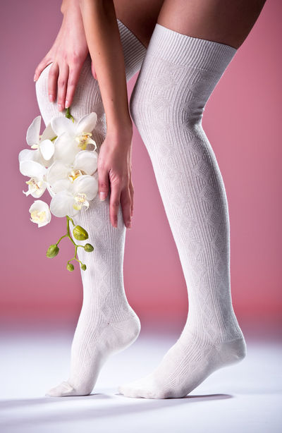 Beautiful woman legs in cotton stockings and white orchid Leg Slim Stockings Woman Caucasian Close-up Cotton Demonstration Flower Hosiery  Human Body Part Indoors  Kneesocks Legs One Person Orchid Flower Pose Posing Slender Socks Studio Shot Woman's Body Part Women Young Adult Young Women