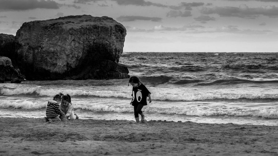 Girls playing on shore at beach against sky