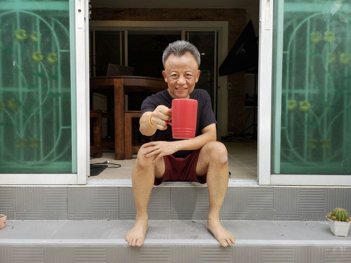 Portrait of smiling mature man holding coffee cup while sitting on doorway