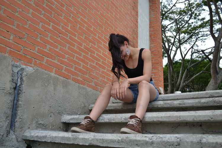 Woman sitting on staircase against wall