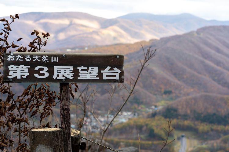Information sign on landscape against mountains
