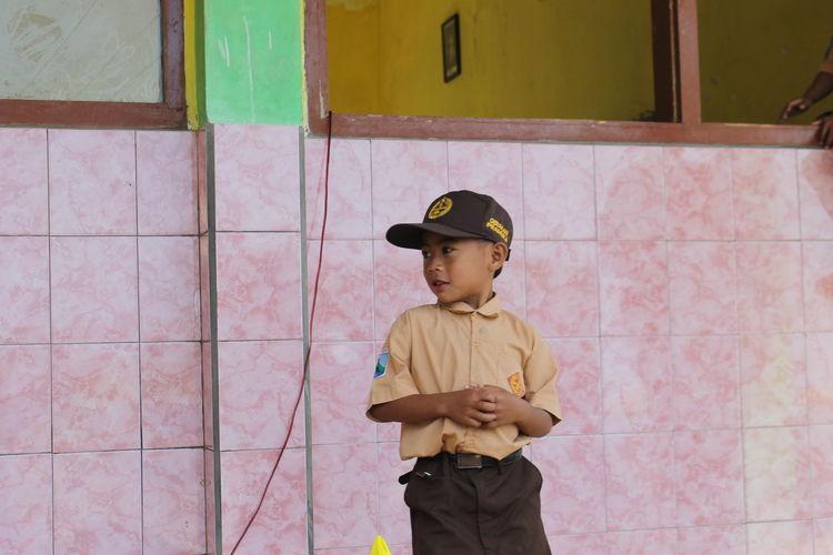 Full length of boy standing against wall