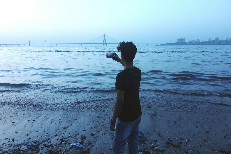 Rear View Of Boy Standing At Beach Against Clear Sky