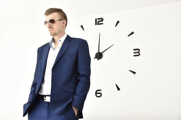 Businessman Standing Against Clock On White Wall