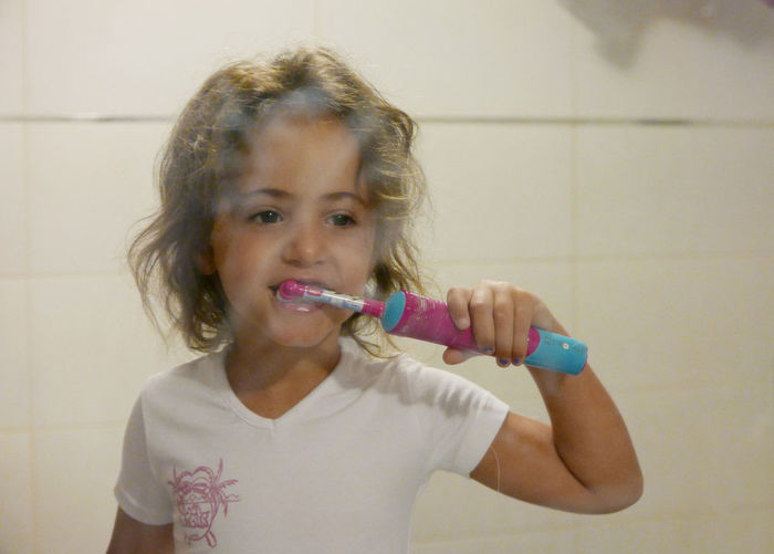 Bathroom Brush Teeth Casual Clothing Child Childhood Facial Expression Indoors  Leisure Activity Lifestyles Mirror Morning Innocence Domestic Life Person Three Quarter Length Standing Human Hair Indoors  Human Face Headshot