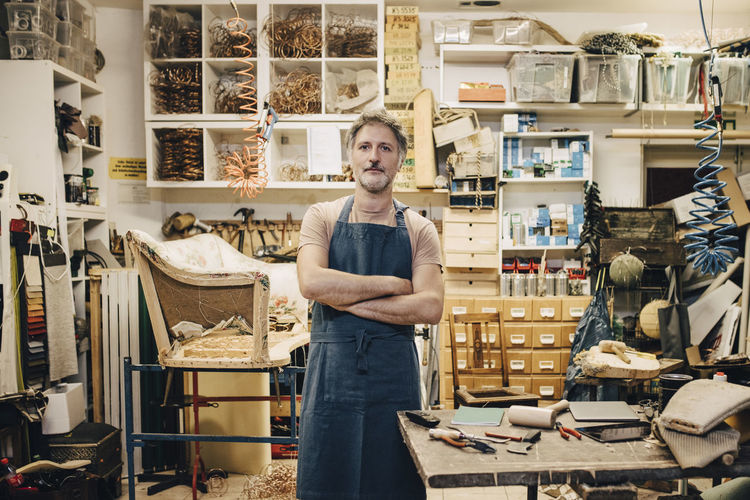 Confident male craftsperson standing with arms crossed in upholstery workshop