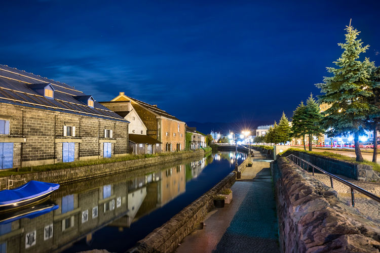 Canal at the hokkaido waterfront and old buildings against sky at night