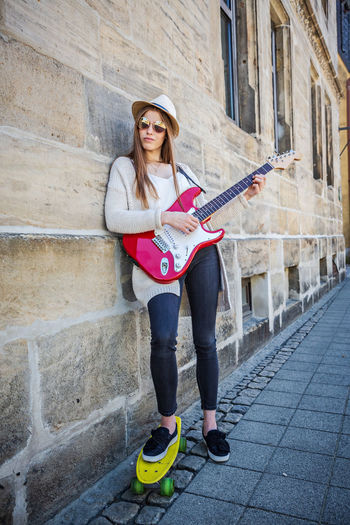 Portrait of young woman playing guitar while standing with skateboard by wall