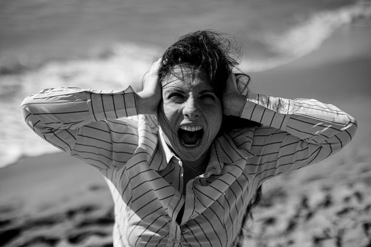 Portrait of frustrated woman with hands covering ears shouting at beach against sky