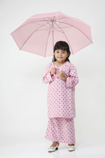 malaysia malay girl holding pink umbrella Asian  Traditional Clothing Baju Kurung Casual Clothing Child Childhood Females Front View Full Length Girls Holding Innocence Looking At Camera Malay Malaysia One Person Protection Rain Rainy Season Real People Security Standing Studio Shot Umbrella Women