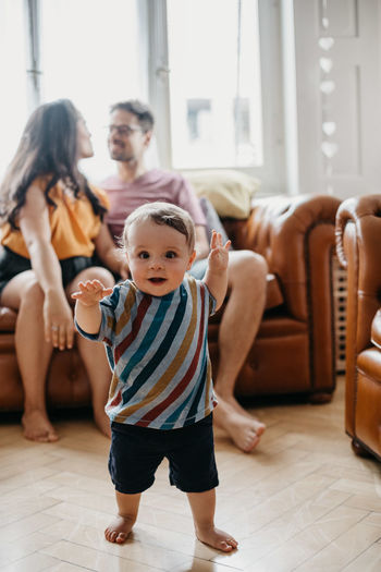 Baby Boy Walking While Parents Sitting On Sofa At Home