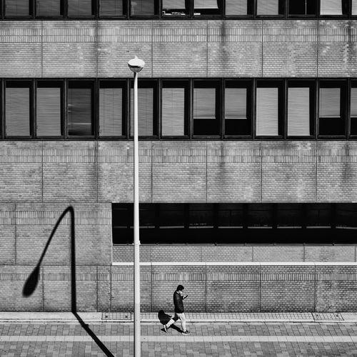 Man walking on footpath by building