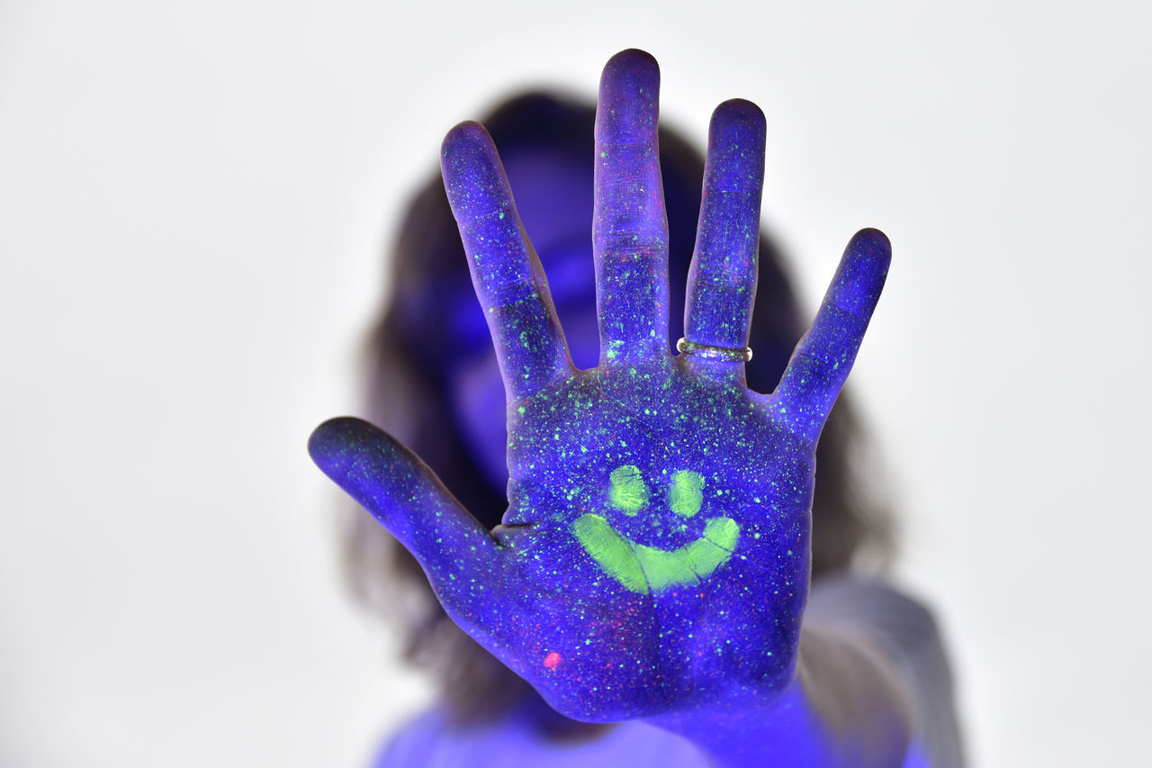 Close-up of woman hand covered with powder paint against purple background