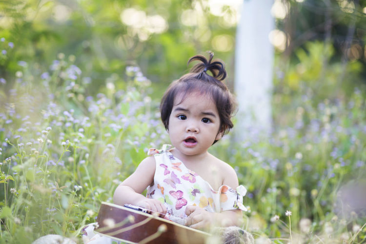 Portrait of cute baby girl sitting on plants