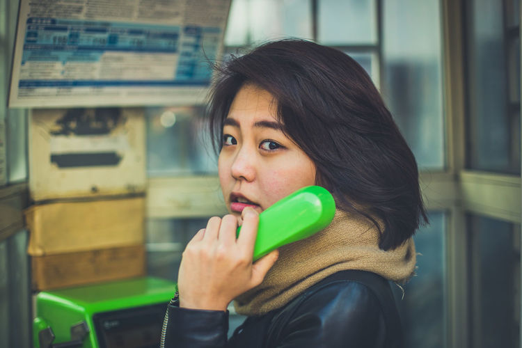 Portrait of young woman talking over telephone in booth