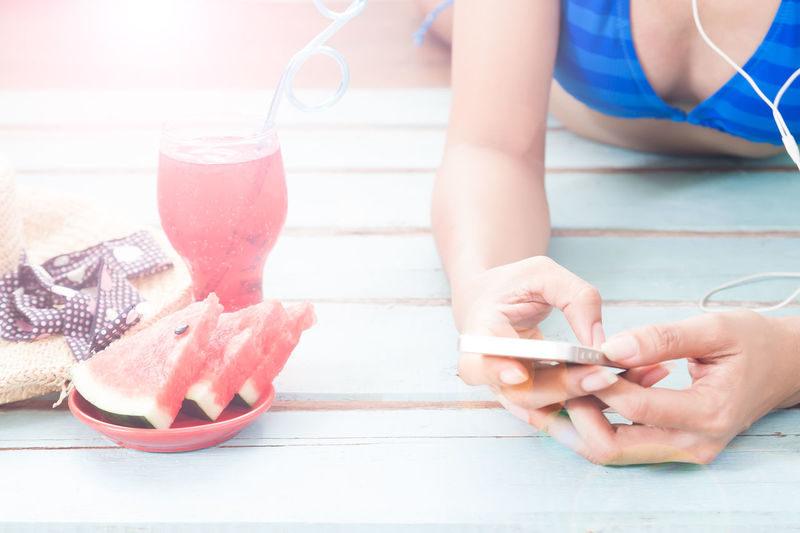 Midsection Of Woman In Bikini Relaxing By Food And Drink On Wooden Floor
