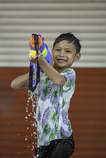 Smiling boy playing with squirt gun