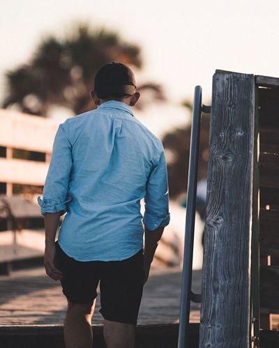 Rear view of man walking on wooden walkway