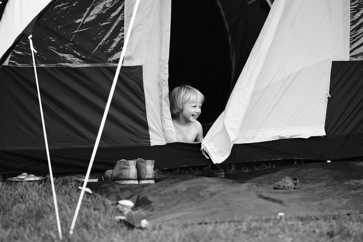Happy shirtless boy looking away while sitting in tent on field