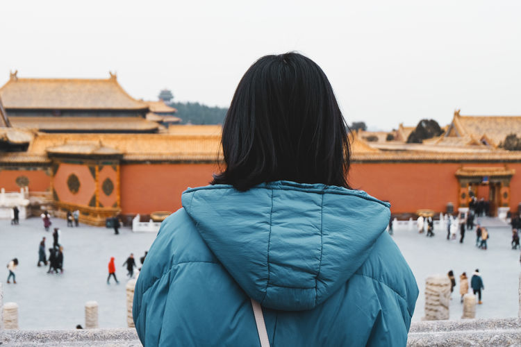 Rear view of woman wearing warm clothing while watching city