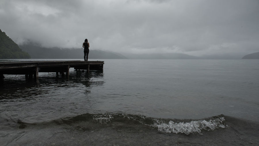 Full length of woman standing on pier by sea against cloudy sky at dusk