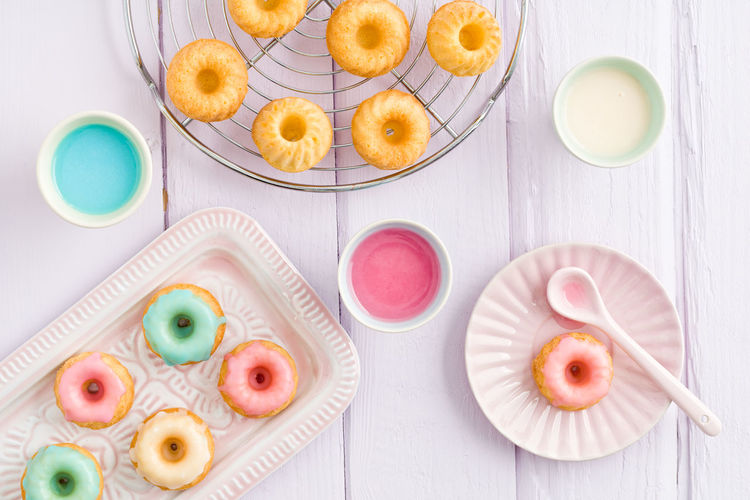 Directly above shot of multi colored donuts with syrups and spoon