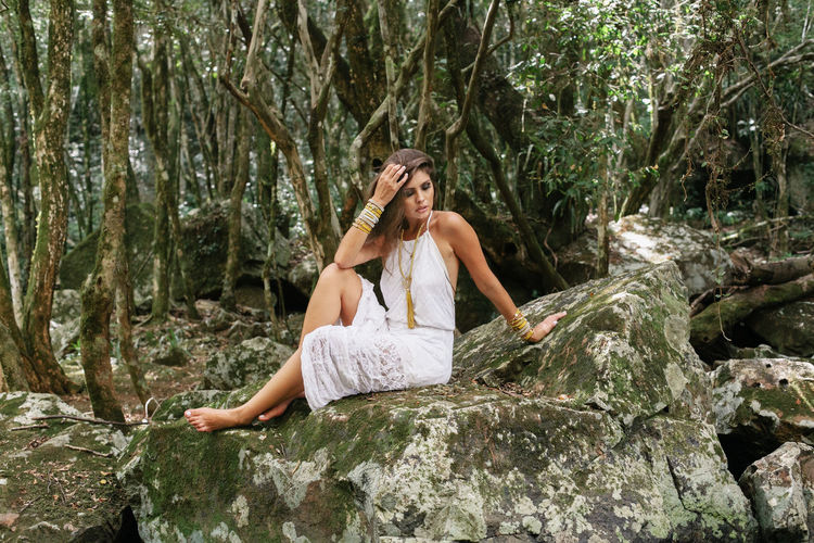 Beautiful young woman sitting on rock in forest