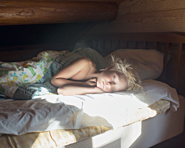 Portrait of young woman sleeping on bed at home