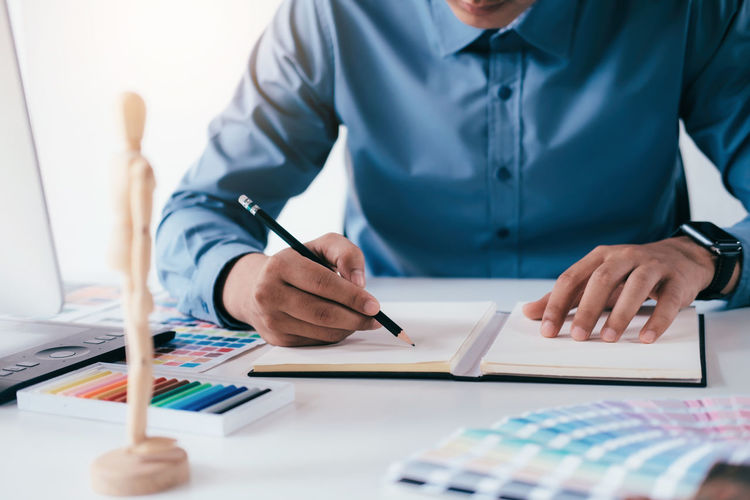 Midsection of businessman drawing in book at office