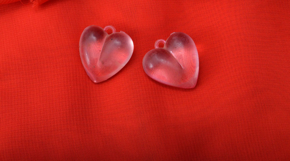 Close-up of heart shape pendants on red textile