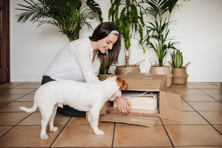 Young woman with dog sitting on floor at home