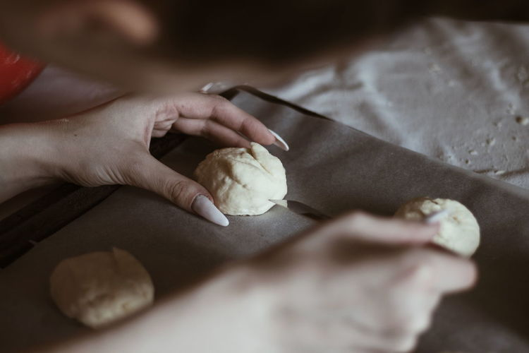 Close-up of hand holding dough on table