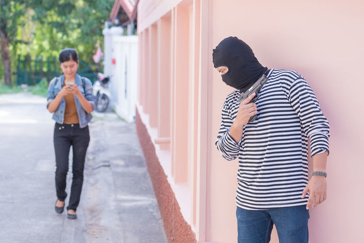 Thief with gun hiding against wall by young woman walking on street by