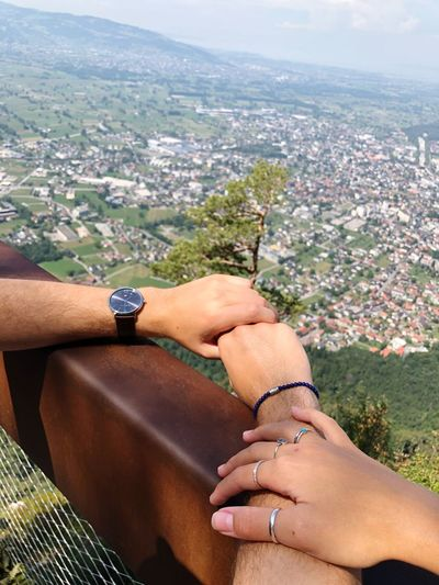 High angle view of couple hands on railing in city